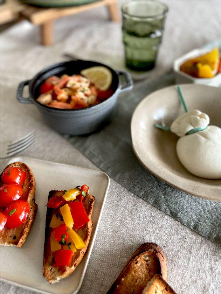 Crostini con peperoni sott'olio, gamberi e burrata di Andria